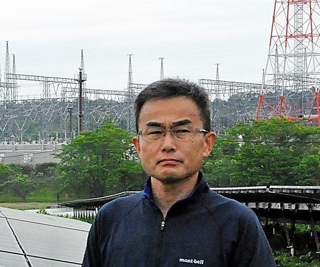 実家近くの東北電力南相馬変電所の前に立つ佐々木秀三さん