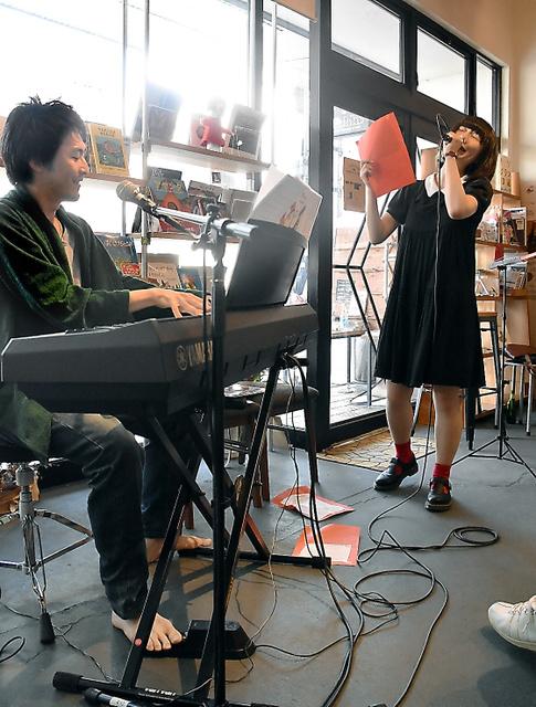 赤い紙に書いた詩を読み捨てていく成宮アイコさん(右)とピアノを演奏する青山祐己さん=2018年6月、金沢市石引2丁目