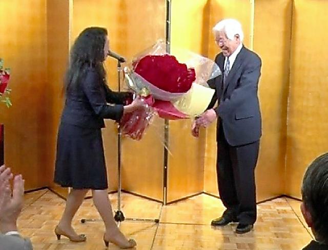 傘寿を祝う会で花束を受け取る佐藤栄佐久さん=5月22日、福島県郡山市(支援者のDVDから)