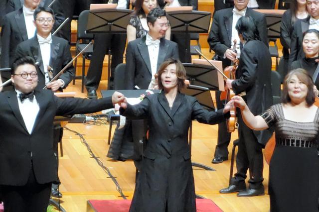演奏が終わり、中国人の歌手と一緒に観衆にあいさつする指揮者の西本智実さん(中央)=23日、北京、西村大輔撮影