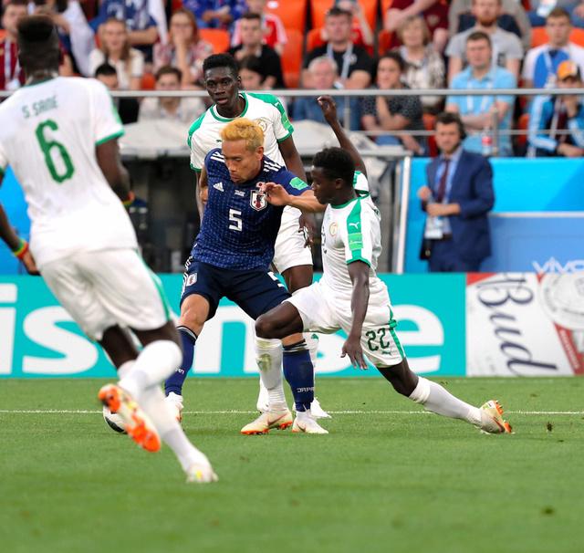 セネガル戦の前半、相手に囲まれながらボールをコントロールする長友(5)。このあと乾が同点ゴールを決めた