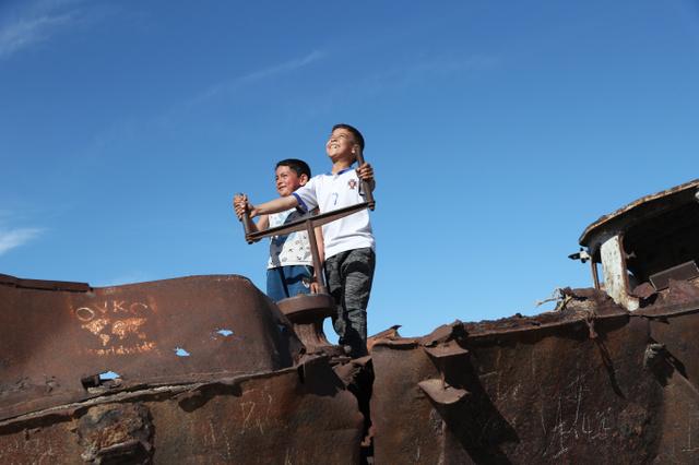 廃船に乗り針路をとる子どもたち=2018年5月、ウズベキスタン・ムイナク市、川村直子撮影