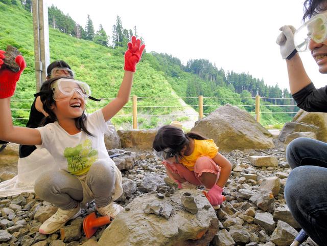 野外恐竜博物館で化石を発掘し喜ぶ親子=福井県勝山市、筋野健太撮影