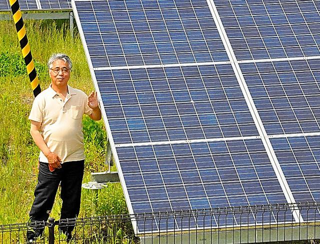 三浦広志さんと、かつて自宅などがあった土地に並ぶ太陽光パネル=5月12日、福島県南相馬市