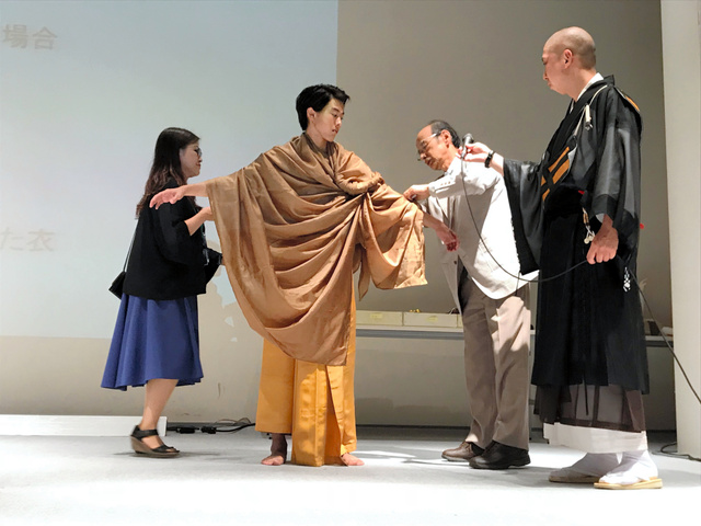 学生モデルに如来の衣装を着付ける山崎隆之さん(右から2人目)。布を巻いただけで装飾のないスタイルが、悟りを開いた姿を示す=2018年6月29日午後、東京都渋谷区の文化服装学院、小滝ちひろ撮影