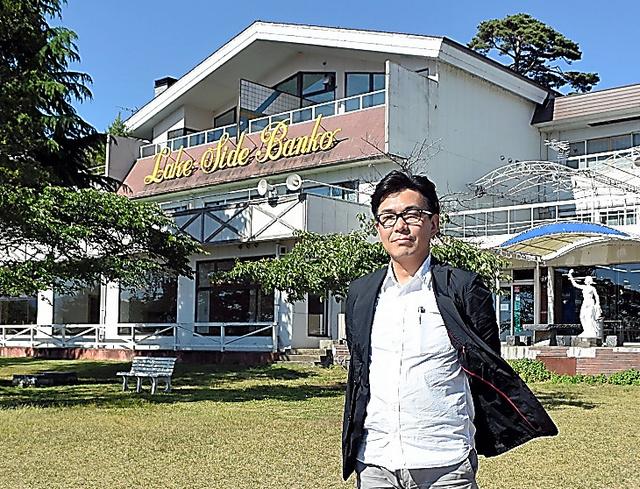 ホテル「レイクサイド磐光」の前に立つ春名秀樹さん=6月、福島県猪苗代町