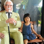 子どもの目線のカーネル人形 ベンチに座る像、初披露