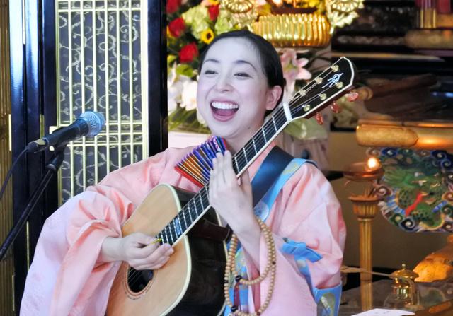 ギターを抱えて歌う法衣姿の三浦明利さん=2018年7月15日、奈良県大淀町の光明寺、小滝ちひろ撮影