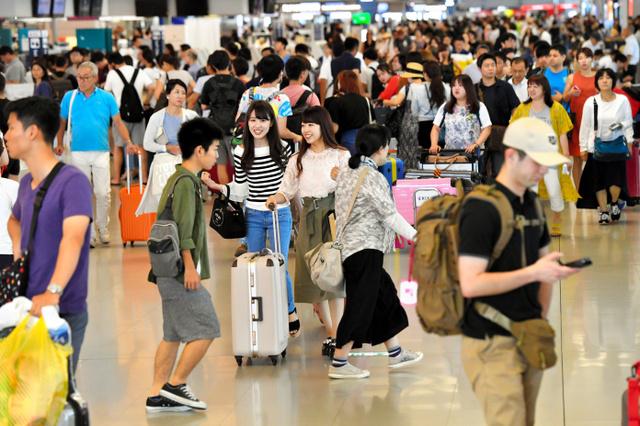 お盆を海外で過ごす人たちでごった返す国際線の出発ロビー=2017年8月、関西空港