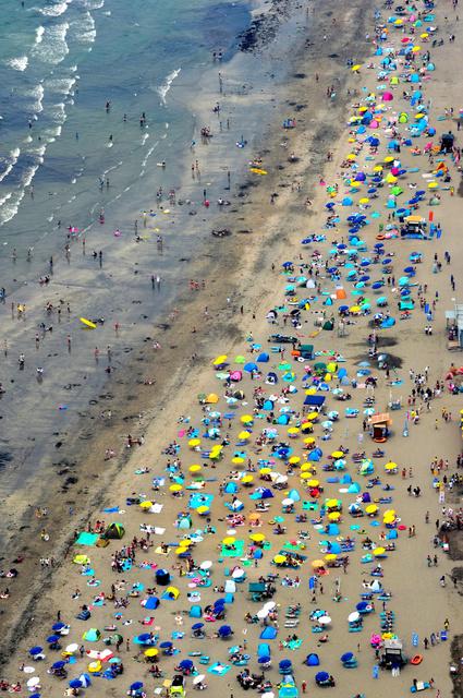 日光が厳しい時期が到来。にぎわう由比ガ浜海水浴場=2018年7月、神奈川県鎌倉市、朝日新聞社ヘリから、山本裕之撮影