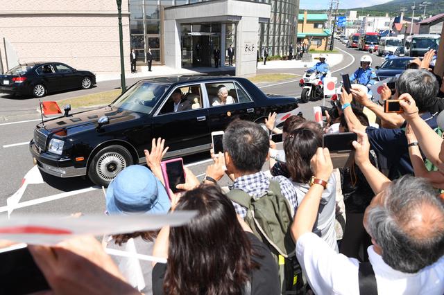 島民らの出迎えに車の中から手を振る天皇、皇后両陛下=2018年8月4日午後、北海道利尻町、白井伸洋撮影