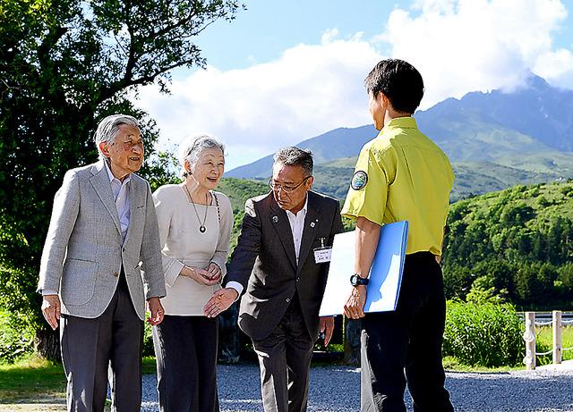 オタトマリ沼を訪問し、環境省の職員から説明を受ける天皇、皇后両陛下。後方は利尻山=4日午後3時16分、北海道利尻富士町、山本裕之撮影