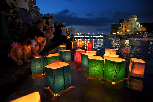 原爆ドームの前を流れる元安川に灯籠(とうろう)を流す人たち=2018年8月6日午後7時36分、広島市中区、小林一茂撮影