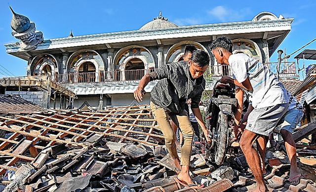 インドネシア・ロンボク島で6日、地震で倒壊したモスク(イスラム礼拝所)のそばで、下敷きになったバイクを取り出す作業をする人たち=ロイター