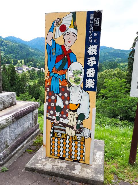 「根子番楽」の顔出し看板。後方に根子集落が広がる=秋田県北秋田市