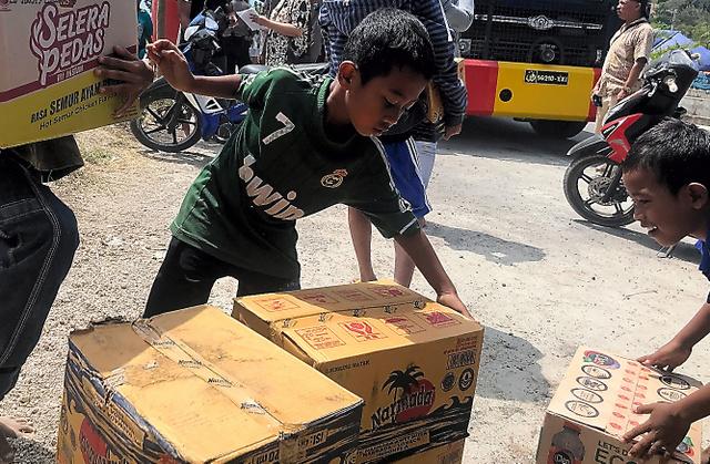 ロンボク島の避難所は水も食料も不足している。民間支援団体が物資を届けると、テントから少年が飛び出して受け取った=8日、守真弓撮影