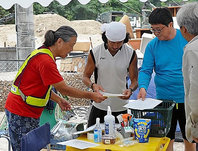 常連のボランティアに指示する「おいちゃん」(左)=7月23日、広島県坂町