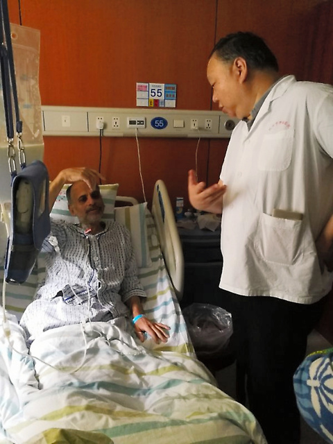 がん患者のサンジュティ・サワール(左)と話す院長の呉式琇=2018年7月、中国浙江省、病院提供
