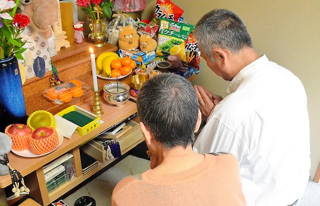 「いまだに亡くなったのが信じられない」と仏壇に手を合わせる両親。「入院後、一度も面会できなかったことが悔やまれる」と母はいう=石川県内、大久保真紀撮影