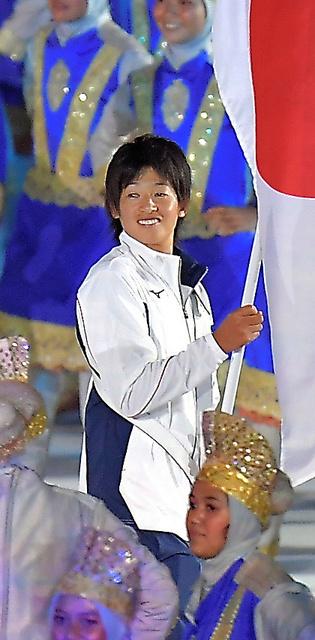 日本選手団の旗手を務める上野由岐子選手=18日夜、ジャカルタのブンカルノ競技場、加藤諒撮影