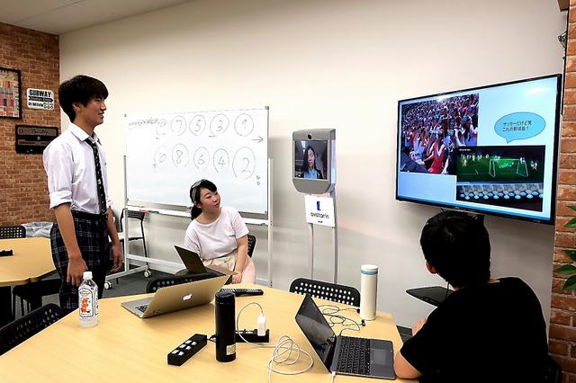 モニターがついた遠隔操作ロボット(中央奥)で授業参加する生徒と一緒に「未来の甲子園」について考える高校生ら=横浜市神奈川区