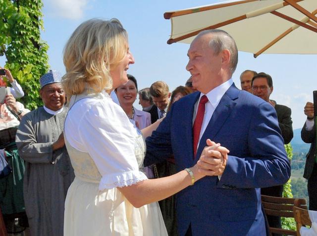 オーストリア南部ガムリッツで18日、実業家の男性との結婚式を開いたオーストリアのクナイスル外相(左)を祝福するロシアのプーチン大統領=AP