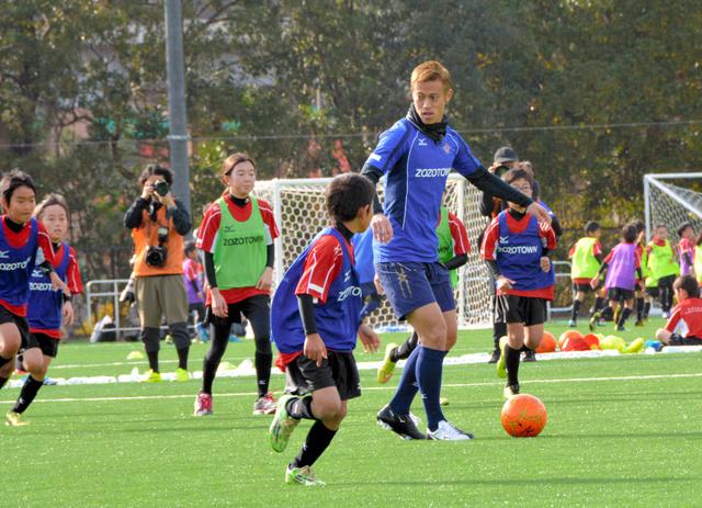 自らの名を冠したサッカー場で子どもたちとプレーする本田=千葉市美浜区