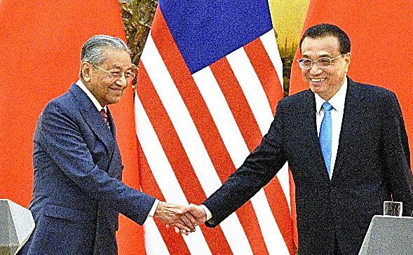 共同会見を終え、笑顔で握手をするマレーシアのマハティール首相(左)と中国の李克強首相=20日、北京、延与光貞撮影