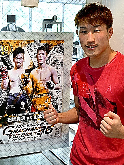 山本聖悟さん。勤務先のフィットネスジムに貼られたタイトル戦のポスターの横で
