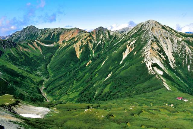 「ワシが羽を広げて飛び立つ姿」と言われる鷲羽岳(右)と、左へワリモ岳、水晶岳。左下の谷が黒部川の最源流部。右の山小屋は三俣山荘。三俣蓮華岳の山頂から写した