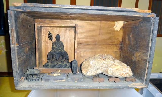 潜伏キリシタンの子孫の家に伝えられてきた木箱。左奥が役行者像、その手前がホラ貝の根付、その右が如来像。右側のアワビの殻の下に金属製の棒3本がある(大浦天主堂キリシタン博物館提供)