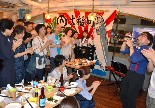 大槌町出身のトランペット奏者・臺隆裕さんの演奏で盛り上がる参加者=東京・赤坂の「東北酒場トレジオンポート」