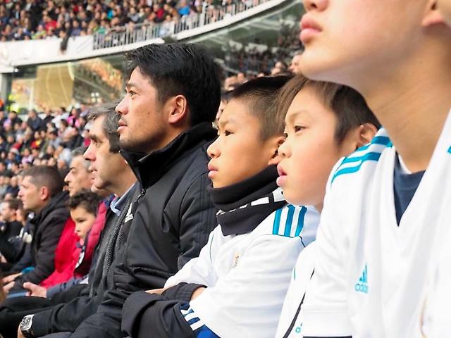 スペインの競技場で、ナチョ選手が出場した試合を観戦する杉山さん(奥)と隣に座る鈴木壱成君ら子どもたち=2017年12月、善福克枝さん撮影