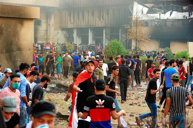 イラク南部のバスラで7日、デモの参加者が暴徒化し、行政機関の建物に火が放たれた=AP