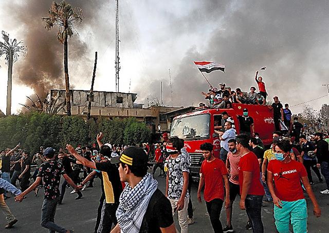 イラク南部のバスラで7日、放火された建物の近くを歩くデモの参加者ら=ロイター