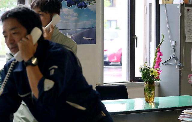 厚真町役場の職員だった中川信行さんの席には花が手向けられていた=10日午後3時14分、北海道厚真町、藤原伸雄撮影