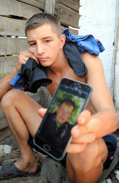 亡くなった父親の写真を見せるアンドレイさん=6月20日、トロイツク、大久保真紀撮影