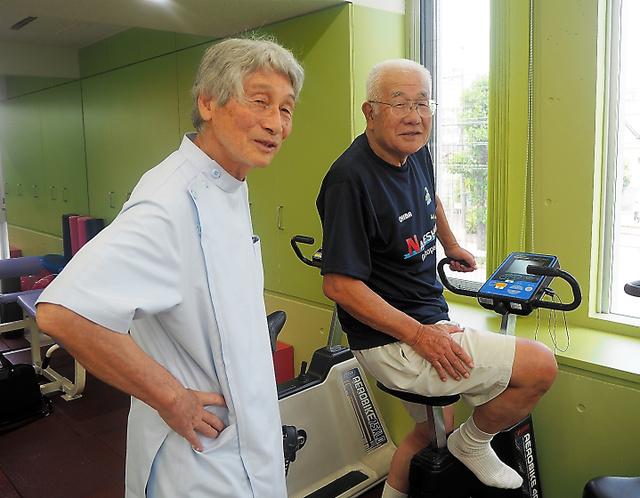 リハビリに励む片伯部さん(右)と、主治医でサッカー仲間の鍋島さん=7月、千葉市中央区