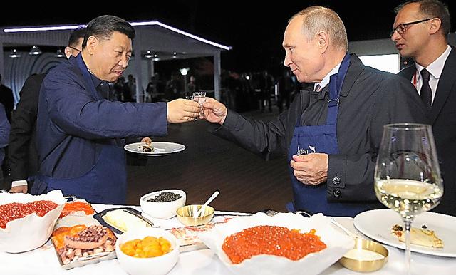 ロシアのウラジオストクで11日に始まった東方経済フォーラムで、展示コーナーの食事を味わいながら乾杯するプーチン大統領と中国の習近平国家主席=AP