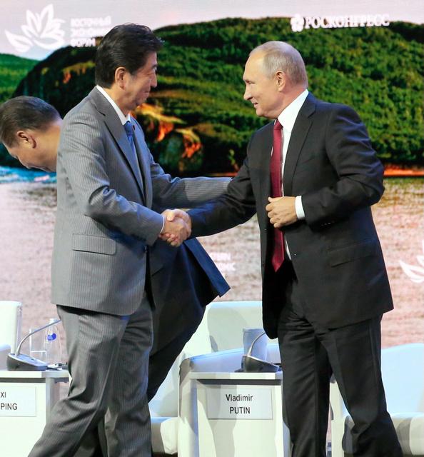 東方経済フォーラムで演説を終え、ロシアのプーチン大統領(右)と握手する安倍晋三首相=2018年9月12日午後4時25分、ロシア・ウラジオストク、代表撮影