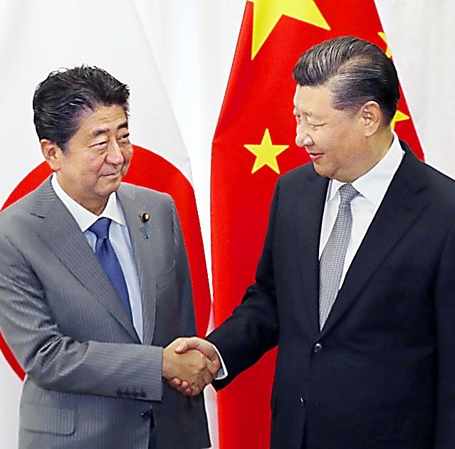 会談で握手する中国の習近平国家主席(右)と安倍晋三首相=12日午前、ロシア・ウラジオストク、代表撮影