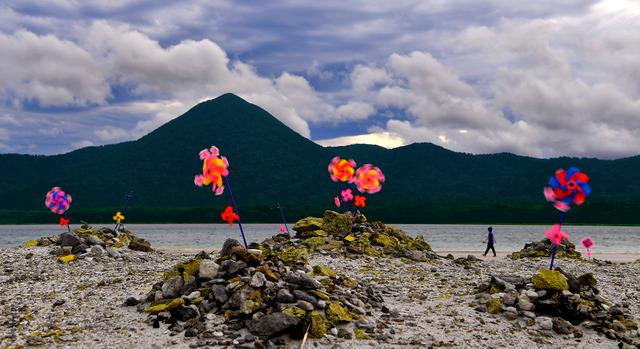 宇曽利山湖が目の前に広がる極楽浜。親子を意味するともいわれる2連の風車が所々に供えられている=青森県むつ市