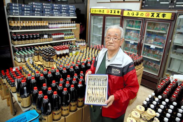 きれいに陳列し直したカツオじょうゆを前に、特産のシシャモを手にする鈴木譲さん=13日夜、北海道むかわ町、三浦英之撮影