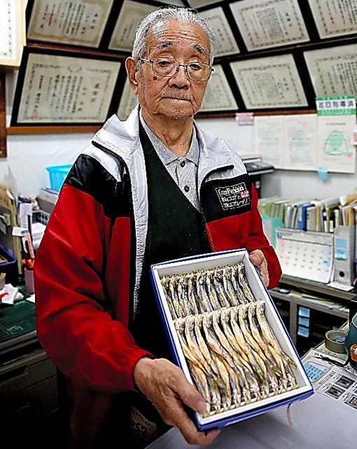 特産のシシャモを手にする鈴木譲さん=北海道むかわ町