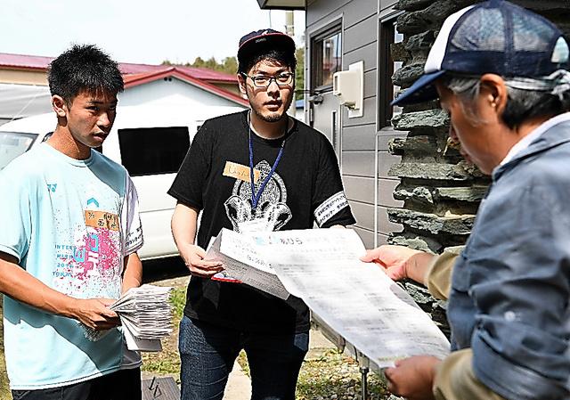 ボランティアに参加し、生活情報が書かれた広報誌を町民らに手渡す金井直樹さん(中央)=15日午前、北海道安平町、白井伸洋撮影