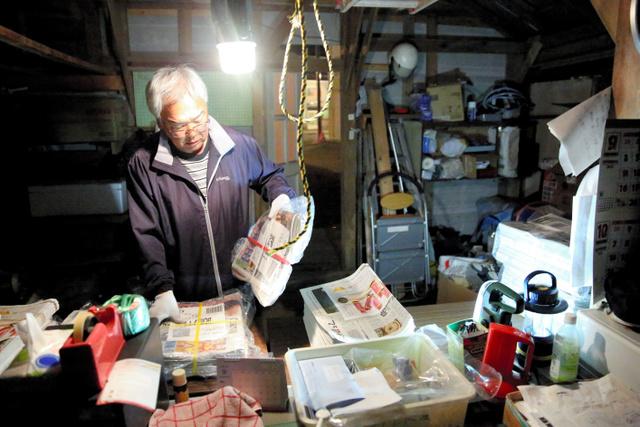 倒壊を免れた倉庫の中で、新聞配達の準備をする工藤弘さん=16日午前1時53分、北海道むかわ町、三浦英之撮影