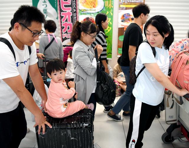 再開した国際線の搭乗手続きカウンターに並ぶ中国人一家。2歳の娘ら家族5人は震災後、パンと水のみで過ごしたという=2018年9月8日午前7時39分、北海道千歳市の新千歳空港、伊藤進之介撮影