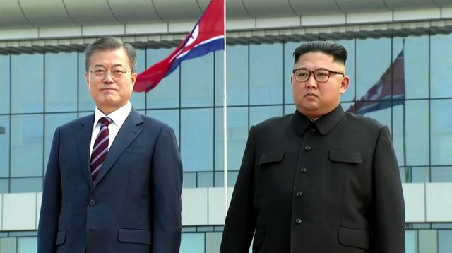 平壌国際空港で18日、並んで記念撮影に応じる韓国の文在寅大統領(左)と金正恩朝鮮労働党委員長=平壌写真共同取材団撮影