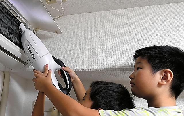 エアコン掃除の第一歩。カバーを開け、大きなホコリを掃除機で吸い取る