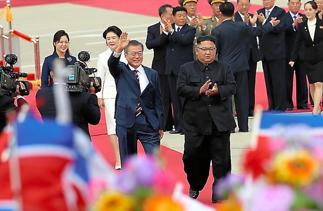 平壌国際空港で18日午前、手を挙げて市民らの歓迎に応える韓国の文在寅大統領(中央左)と金正恩朝鮮労働党委員長=平壌写真共同取材団撮影